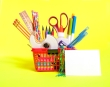 A fun red shopping basket full of school supplies.